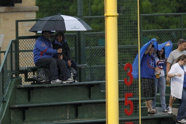 Fans cover up in the left field bleachers at Wrigley Field, after a torrential downpour hit the Friendly Confines shortly after 12:40 p.m. in Chicago on Sunday.
