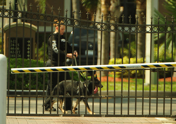 A Pembroke Pines police officer and dog search the gated apartment complex where a shooting took place Sunday, May 6, 2012.