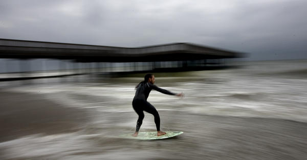 Skim boarder David Martinez speeds past on his board into the receding line of surf on Buckroe Beach as Hurricane Earl kicked up the surf early Friday.