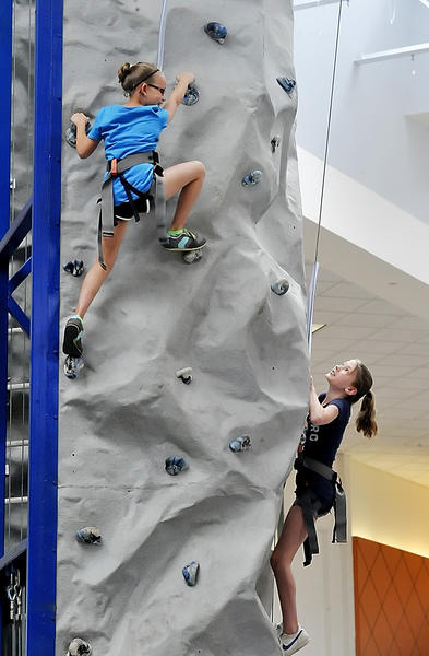 Mackenzie Mooers, 10, of Clear Spring, left, and Lindsey Frey, 11, of Waynesboro, Pa., climb a 24-foot rock wall set up in Valley Mall Sunday for Family Fun Day.
