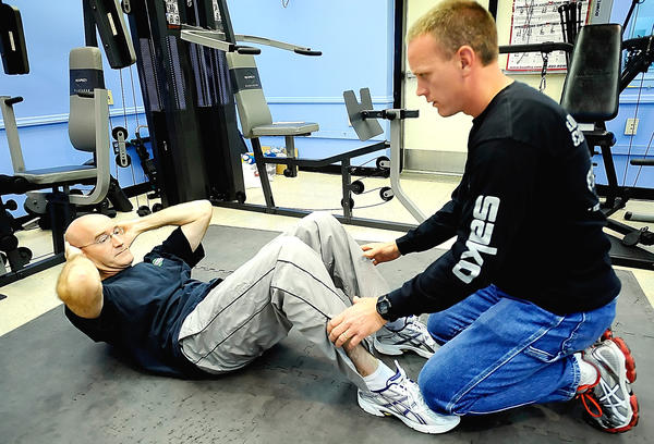 Hagerstown Police Department Officer Robert McKenzie, left, takes the sit-up portion of the department's annual fitness test. Sgt Jim Robison, one of the police department's four physical training officers, is at right.