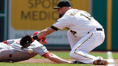 The ball gets past Pittsburgh Pirates first baseman Casey McGehee (14) on a pickoff throw by Charlie Morton as Cincinnati Reds Drew Stubbs dives back in the first inning on Sunday.