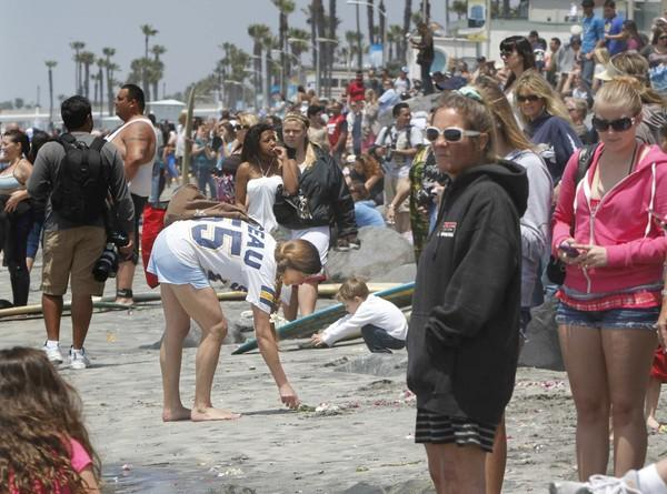 A woman wearing a Junior Seau San Diego Chargers jersey rearranges a bouquet of flowers on the sand after a wave moved it.