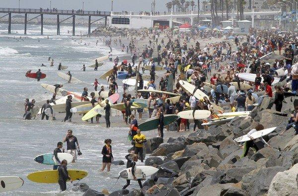 Surfers and spectators crowd The Strand, just south of the Oceanside pier to honor Junior Seau, a local NFL hero who died from a self-inflicted gunshot last week.