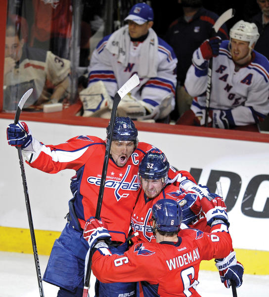 Washington's Mike Green, center, celebrates his game-winning goal with Alex Ovechkin (8), and Dennis Wideman (6) to tie the Caps' playoff series with New York.