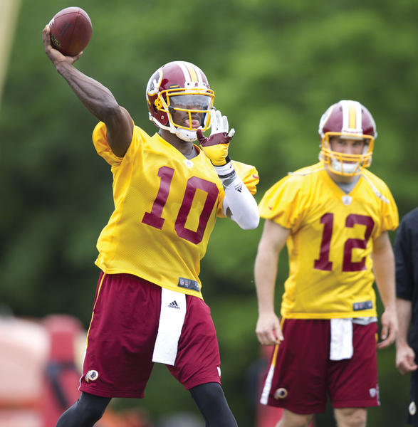 Washington quarterback Robert Griffin III (10) throws in front of quarterback Kirk Cousins (12) during the last day of the Redskins' rookie training camp.