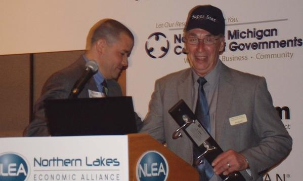 "Pellston village president Jim Gillett accepts the ""Maniac of the Year"" award Friday at the Northern Lakes Economic Alliance annual luncheon at Boyne Mountain in Boyne Falls. The lighthearted ""maniac"" title honors a recipient with a strong commitment to economic development."