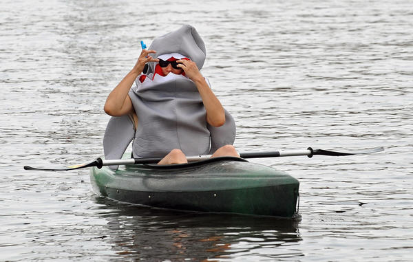 A kayaker serving as a safety monitor at the Canton Waterfront Park for the 2012 Baltimore Kinetic Sculpture Race watches the race as a shark.