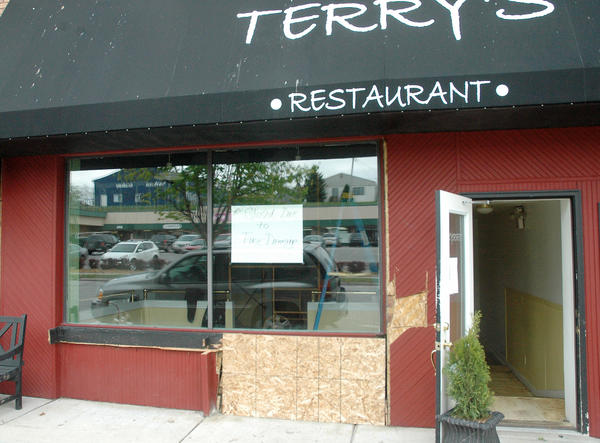 A board covers a section of wall damaged by an fire that started in a flower box outside Terry's Restaurant in downtown Charlevoix early Saturday, May 5.
