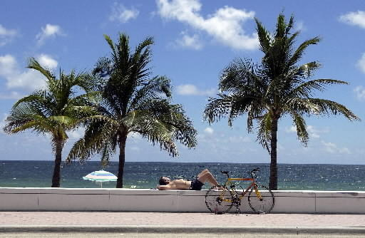 A man lazes in the sun at Fort Lauderdale's beach. Expect another hot afternoon.