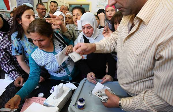 Syrian women have their identification checked before casting their votes in Damascus in parliamentary elections.