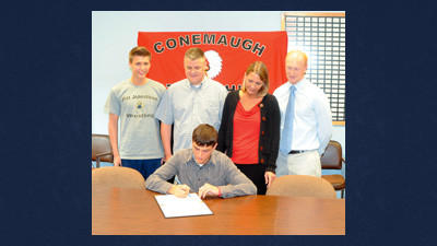 Conemaugh Township senior Cory Berchick, seated, signs a letter of intent to wrestle for the University of Pittsburgh at Johnstown. He is joined by, from left, brother Casey, father Shawn, mother Rachel and wrestling coach Jarod Feathers.
