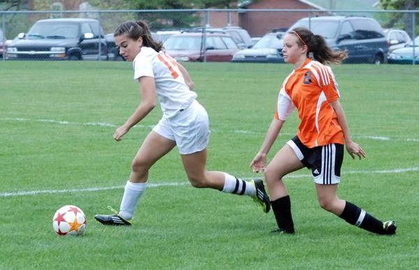 Harbor Springs senior Lyndsay Hall (left) pushes the ball away from Elk Rapids senior Robin Trierweiler during the first half of a Lake Michigan Conference match Monday at Ottawa Stadium in Harbor Springs. The Rams won in overtime, 2-1.