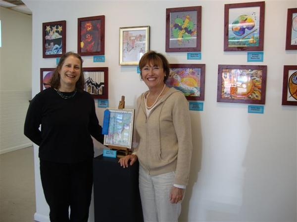 Deb Bobo (left), SOBO Art Fest poster contest winner, accepts her award from Boyne Arts Collective curator Mary Whitlock.