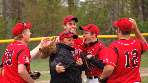 J-L coach Rick Guild celebrates with players (l-r): Garrett Koronka, Gunner Owens, Brett Kortman and Blake Huff after the Cardinals defeated rival Mancelona 5-4 in extra innings in game one of Monday's Ski Valley Conference doubleheader.