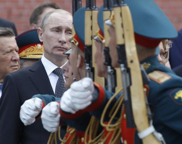 Russian President Vladimir Putin watches soldiers march past during a ceremony at the Tomb of Unknown Soldier on the eve of the Victory Day celebrations in Moscow.