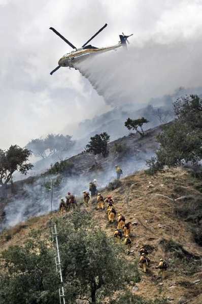 A Los Angeles County ground crew makes it's way the hillside of a small, but very fast moving brush fire behind JPL on Monday, May 16, 2011 as a Los Angeles County helicopter drops a load of water on a hot spot. The NASA fire department, and the Los Angeles County Fire Department battled the fire with water drops from helicopters, and ground crews. (Tim Berger/Staff Photographer)