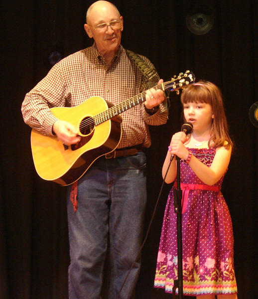 "The Rev. Paul Bauer plays the guitar while his granddaughter, first-grader Mariah Ryland, sings ""This Land is Your Land"" at the Salem Avenue Elementary School talent show."