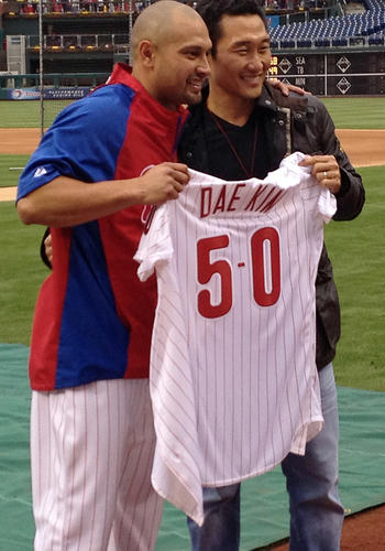 Daniel Dae Kim is presented with a special game jersey for the occasion by Victorino.
