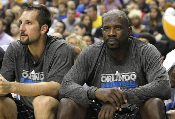 Orlando Magic players Ryan Anderson and Jason Richardson watch from the bench.