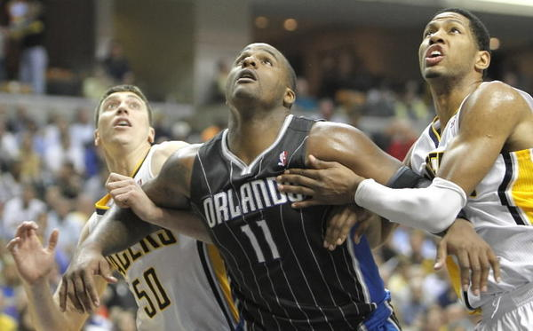 The Indiana Pacers' Tyler Hansbrough (50), Orlando Magic's Glen Davis, (11) and Indiana'a Roy Hibbert, right, look for a rebound.