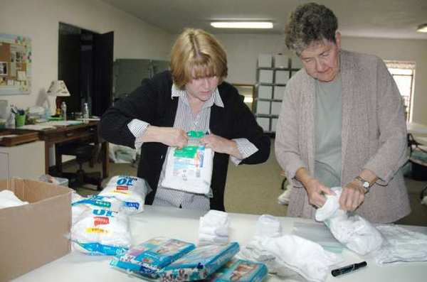 Preparing clothing for Assistance League of Glendale's Operation School Bell are, from left, Patty Schermer, chairwoman; and Rae McCormick, dresser.