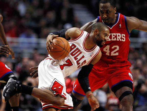 Chicago Bulls point guard C.J. Watson goes against Philadelphia 76ers power forward Elton Brand at the United Center.
