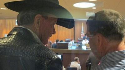 Ron Bergeron, left, talks with his son Lonnie at the Broward County Commission meeting.