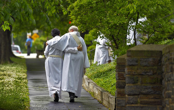 A priest and deacon walk together beneath a light rain, following a Eucharist of the Resurrection of Rev. Dr. Mary-Marguerite Kohn at The Cathedral of the Incarnation May 8, 2012.