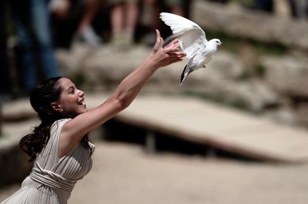 An actress acting as a priestess releases a dove on May 9, 2012 during the lighting ceremony in ancient Olympia the sanctuary where the Olympic Games were born in 776 B.C.