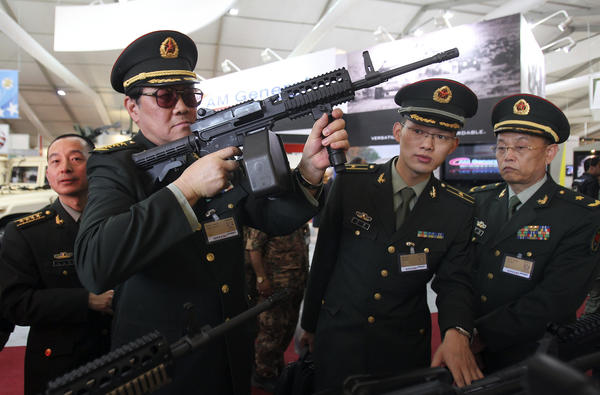 Chinese officers check rifles of ARES Defense Systems, Inc from the U.S. at the opening of the Special Operations Forces Exhibition and Conference at King Abdullah I Airbase in Amman.