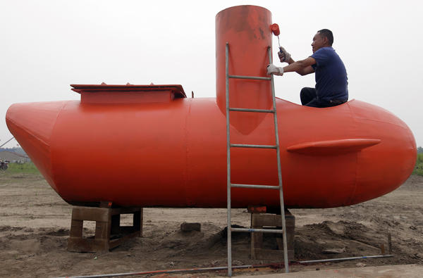 A worker paints a single-seater submarine designed by Zhang Wuyi and his fellow engineers at a shipyard in Wuhan, China. Zhang, a 37-year-old local farmer, who is interested in scientific inventions, has made six miniature submarines with several fellow engineers, one of which was sold to a businessman in Dalian at a price of 100,000 yuan ($15,855) last October.