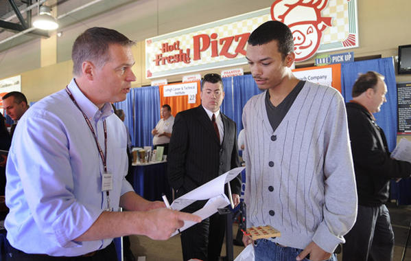 Greg Schaffer of United States Cold Storage of Bethlehem, left, discusses a job application with Ismanuel DeJesus of Allentown at Coca-Cola Park Wednesday.    The Morning Call and CareerBuilder hosted the 5th annual career fair there.