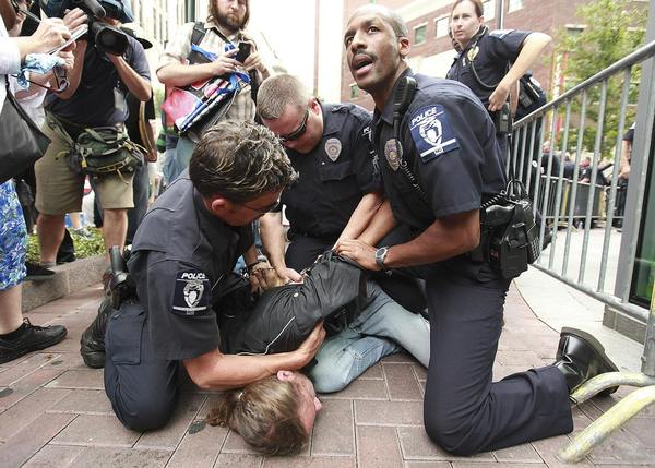 A protester is detained and arrested by Charlotte-Mecklenburg Police Department officers after he tried to trespass onto private property outside the Bank of America annual shareholders meeting in Charlotte, North Carolina.