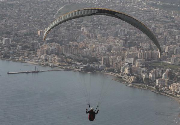A paraglider flies over the city of Vlore during an annual Balkan competition, some 150 km (93 miles) from Tirana, Albania.