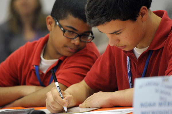 Domingo Delgado, 12, left, looks on as his team mate Paolo Brandon, 12, both seventh graders at Noah Webster School, writes down the groups answer in the 7th and 8th grade Geography competition.