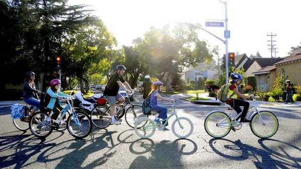 A group of R.D. White Elementary School students cross Glenoaks Boulevard on Geneva Sreet in Glendale on Wednesday for the first National Bike to School Day. 30 students, it was estimated, rode their bikes to school, several for the first time.