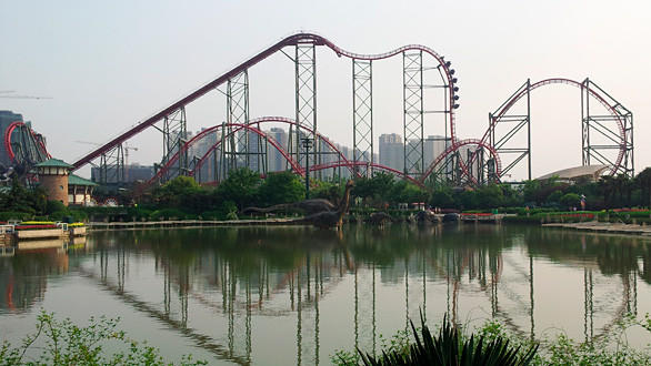 Riders rotate in their seats as the Dinoconda fourth-dimension roller coaster descends down a drop at China's Dino Land.
