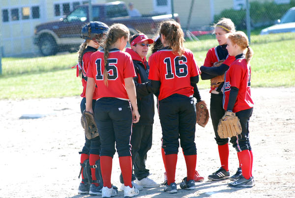 Veteran East Jordan softball coach Meg Kitson (middle) talks to her team during the opening game of Wednesday's Lake Michigan Conference doubleheader against Harbor Springs at the East Jordan High School.