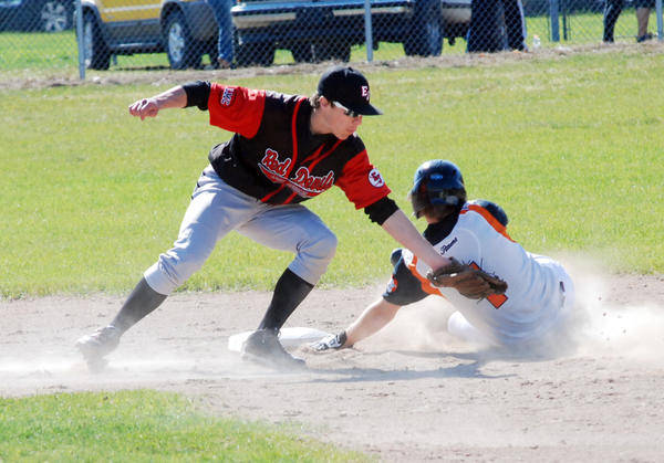 East Jordan second baseman Austen Mellios (left) tags out Harbor Springs senior Scott Morse at second base on a steal attempt during the opening game of a Lake Michigan Conference doubleheader Wednesday at East Jordan High School.