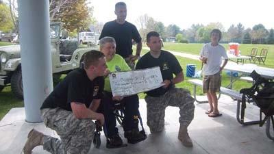 Michigan Paralyzed Veterans of America Executive Director Mike Harris (second from left) accepts a contribution from U.S. Army Sgt. 1st Class Donald Holley (left), Sgt. 1st Class Russell Tansey (third from left) and Staff Sgt. Kenneth Hubbard in May 2011 along the Petoskey waterfront. Holleys son, Slade, is shown at the right. The soldiers raised the funds in conjunction with a weighted march from Indian River to Petoskey in 2011 and plan to repeat the fundraising event this year on Saturday, May 19.