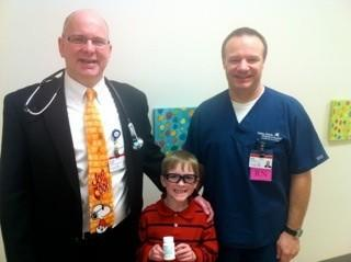 Kurtis Mainland, 7, holds a bottle of the recently FDA-approved drug, Kalydeco, while standing with his doctor, John Schuen (left) and his favorite nurse, Brian Postma.