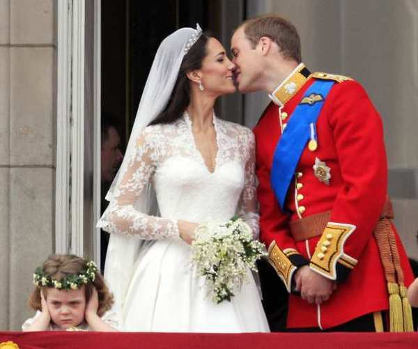 Prince William kisses his wife, Kate Middleton, as a young member of the wedding party frowns -- maybe because she was so overwhelmed by the cost of the big day.
