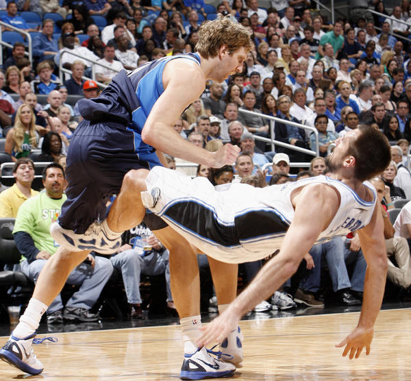 Dallas forward Dirk Nowitzki (41) knocks Orlando forward Ryan Anderson (33) to the floor while drawing the foul during the Mavericks' 98-100 victory over the Magic in Orlando, Fla. Friday, March 30, 2012.