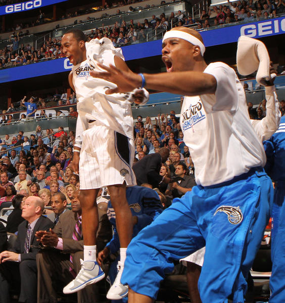 Orlando's Dwight Howard, left, and Quentin Richardson jump off the bench in celebration during the first half of the Magic's game against the Cleveland Cavaliers in Orlando, Fla. Friday, February 2, 2012.