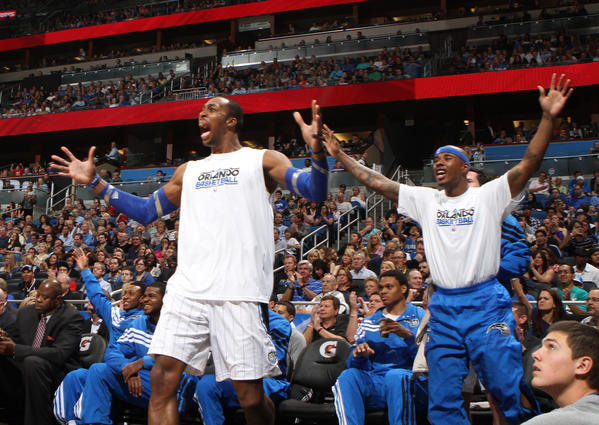 Orlando center Dwight Howard, left, and Quentin Richardson react to a Glen Davis dunk during the first half of the Magic's game against the New Jersey Nets in Orlando, Fla. Friday, March 16, 2012.