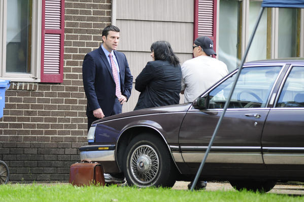A Ryan McGuigan (L), attorney for Robert Gentile, talks with Patricia Gentile and Robert Gentile's son while federal and local law enforcement authorities search the Manchester, Ct, house of Robert Gentile.