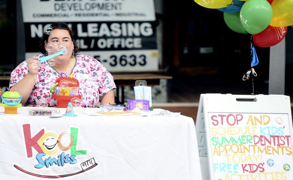 Community Relations Specialist Jennifer Kram blows bubbles to attract passersby and encourage them to make a dentist appointment Thursday during Maymart in downtown Hagerstown.