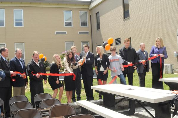Somerset senior Elizabeth Snyder took a cut at the ribbon cutting for a two-year long project that cumulated in a dedication that drew a large crowd to the Somerset Area Junior/Senior High School courtyard Thursday. From left were, Senior High Principal Mark Gross, John Wendell of the Somerset County Rotary Club, Kevin Braken, Lowes manager, Snyder and her project classmates, Alexis Oropallo, Garrett Baird, Zachary Slayback and Aubrey Stull, beside Quinn Berkey, Somerset senior who helped with laying the pavers and landscaping, Jerry Pyles, State Farm, and Lou Sheetz, co-owner of Sheetz and Somerset School Superintendent Krista Mathias.