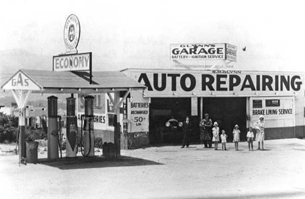 The Glynn family in front of the garage and service station that Raymond Glynn operated on Foothill Boulevard near Day Street. Left to right, Joseph Forster, a nephew who helped at the garage on weekends; Raymond, Sr., holding their dog Jiggs, Mary Ellen, John, Jeraldine, Raymond, Jr. (Bud), and Marcella, holding baby Eileen. The Glynn home was near the service station. Photo 1931.